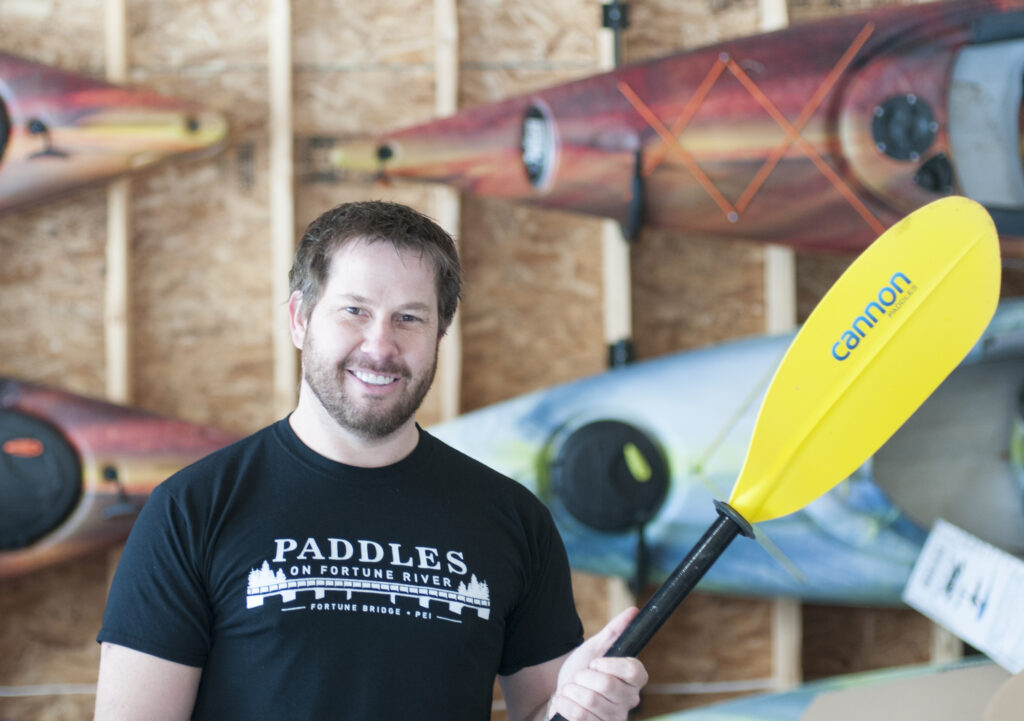 Image of man with paddle, recipient of Small Business Investment Grant